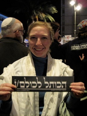 "Me at a march for religious freedom in Jerusalem, spring of 2010. The bumper sticker says ""Ha-kotel l'kulam/n -- the Kotel for all"" with all being written in both the masculine third person plural and the feminine third person plural."